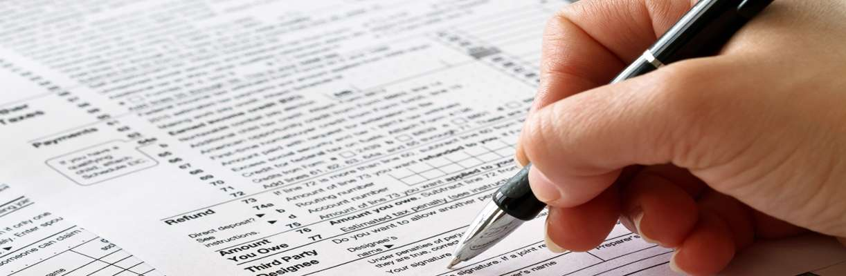 A person's hand and pen are shown working on a tax form