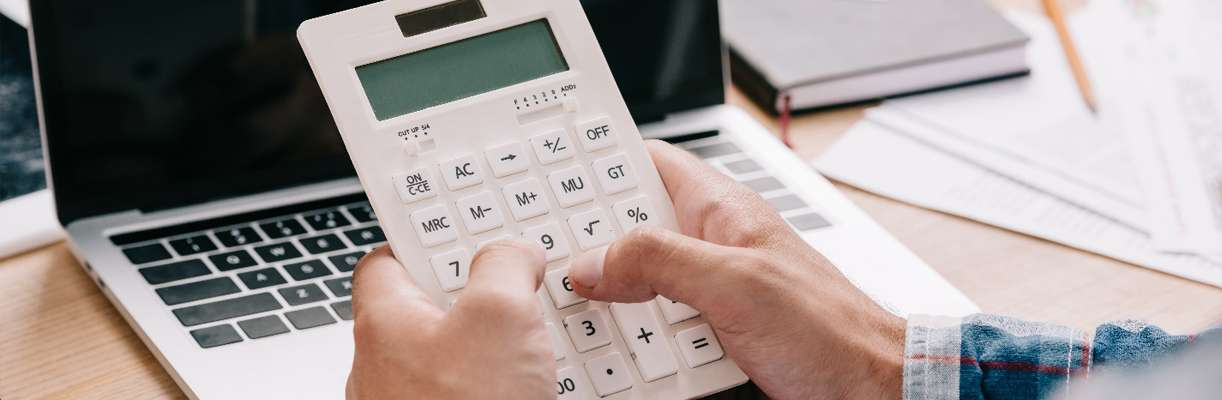 A person seated at a desk holds a calculator while evaluating the price of a business