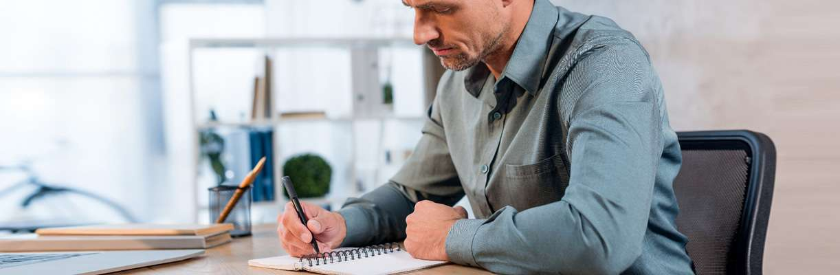 A person sits at a desk in an office and works through the steps of buying a franchise