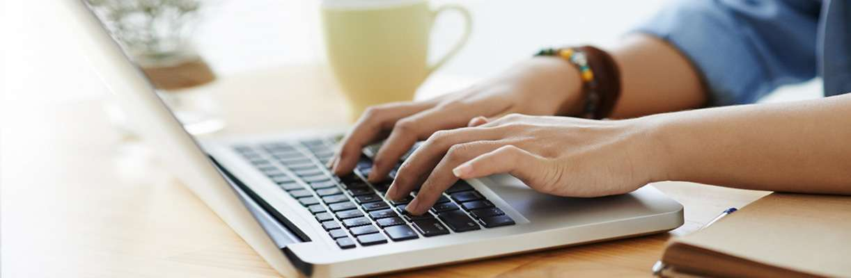 A person types on a computer keyboard to search for franchise opportunities