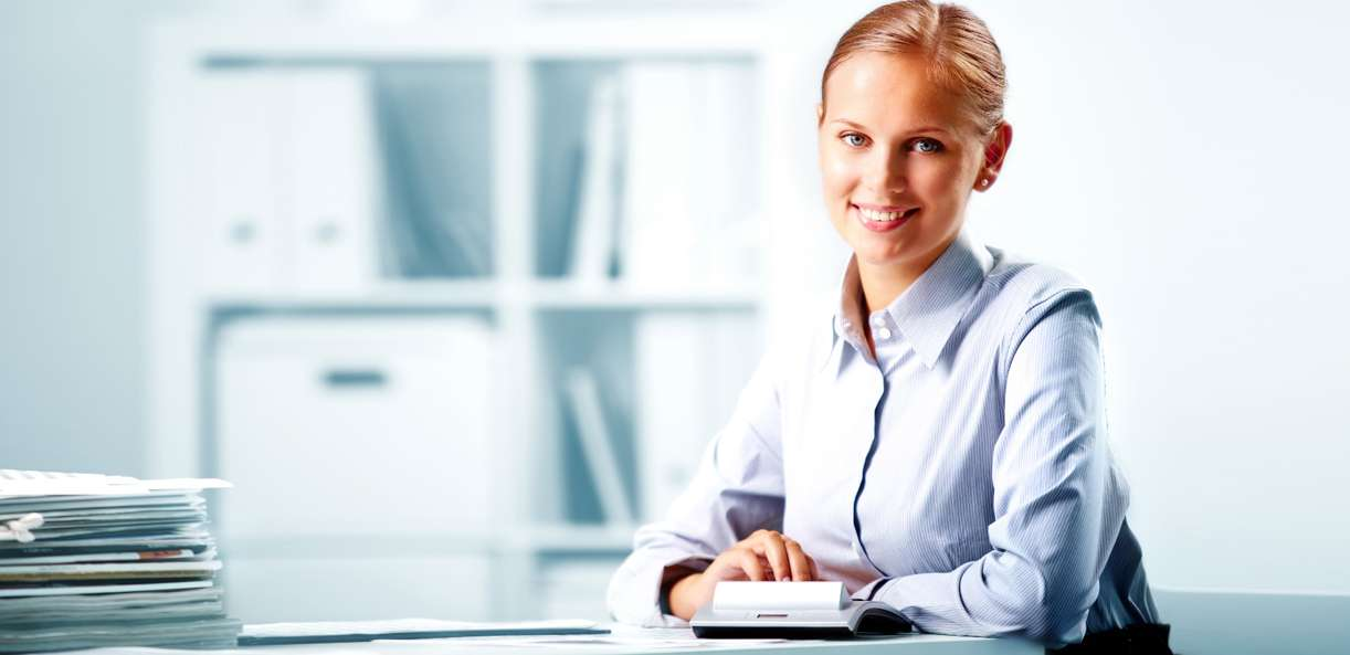 An accountant is sitting at a desk, prepared to help with an acquisition