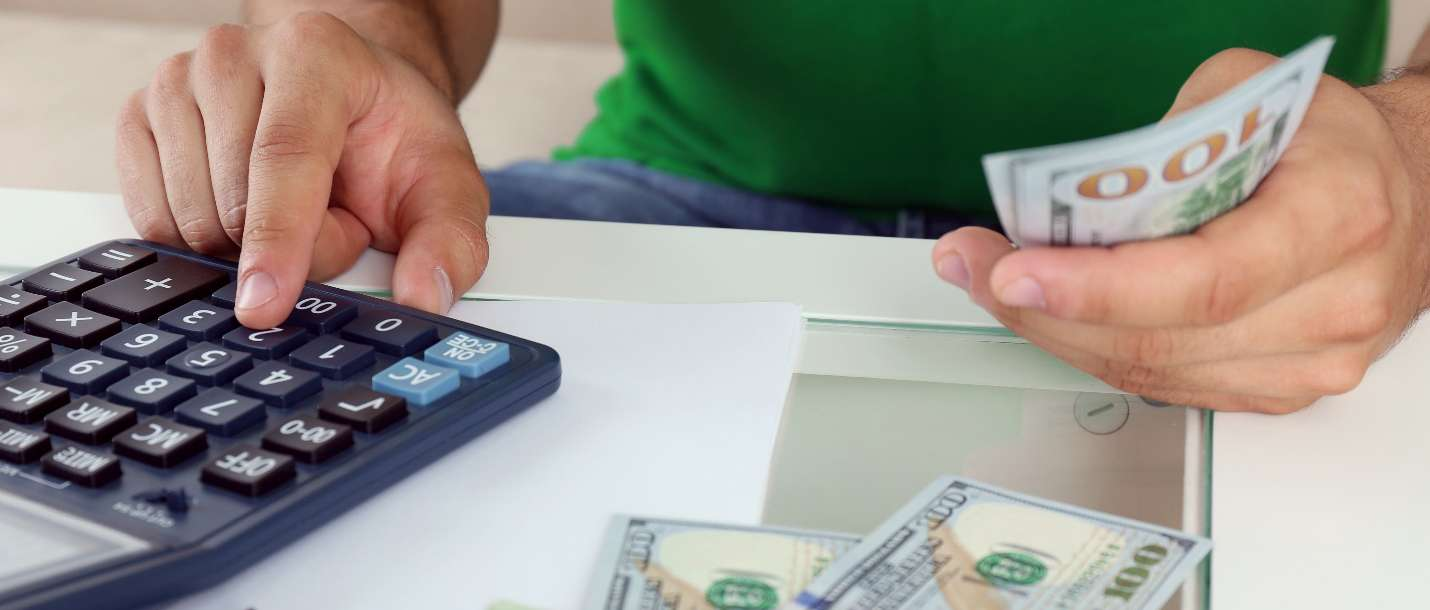A person types on a calculator and holds 100 dollar bills, determining how to save on equipment costs