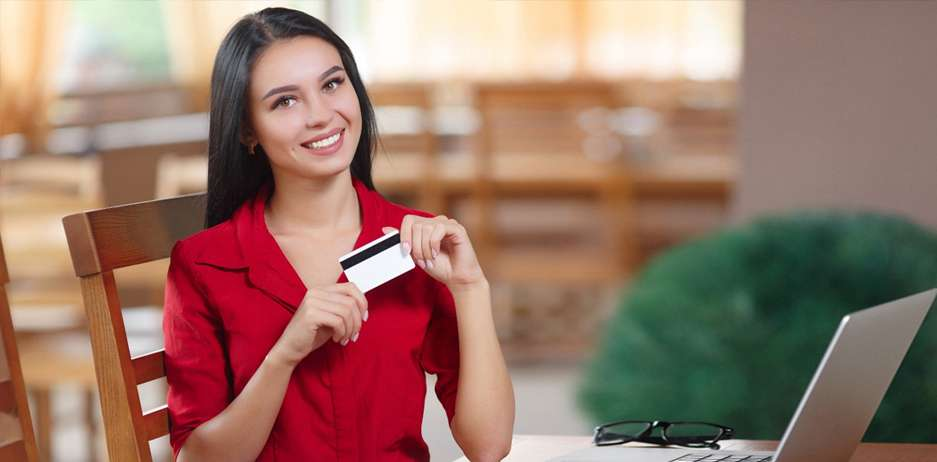 A person holding a credit card is happy after taking the action to sign up for a business credit card