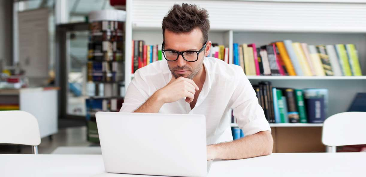 A person at a desk is looking at his computer screen to learn about the fundamentals of buying a business