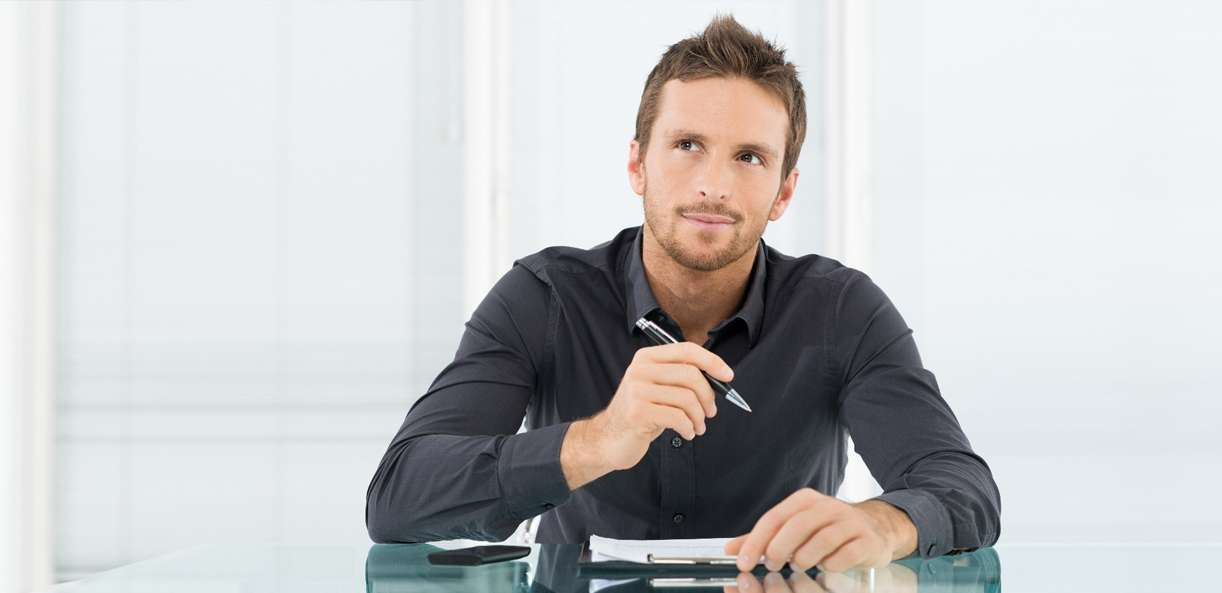 A person sits at a desk with an open portfolio wondering about the mistakes he might make when buying a business