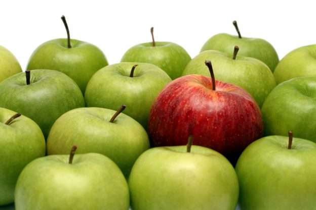 A red apple lays in a pile of green apples to signify how important it is to set your business apart