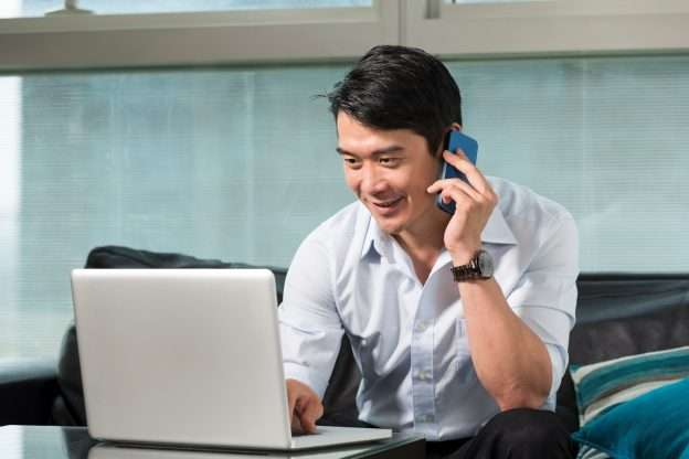 A person uses a phone and computer to determine how to use a retirement savings plan to fund a business acquisition