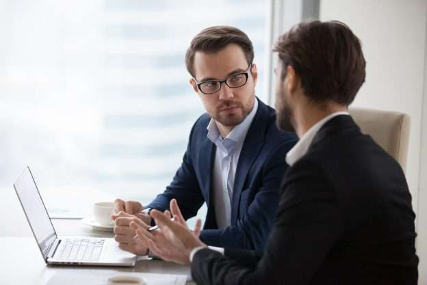 A prospective buyer sits facing a seller, attempting to negotiate to buy a business