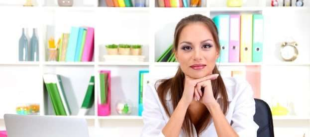 A person sitting at a desk is thinking about how to design a website to amplify her business brand.