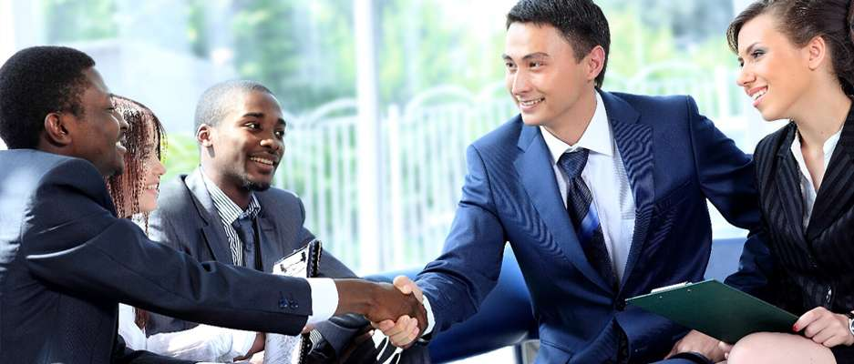 Venture capital professionals shake hands with a business owner