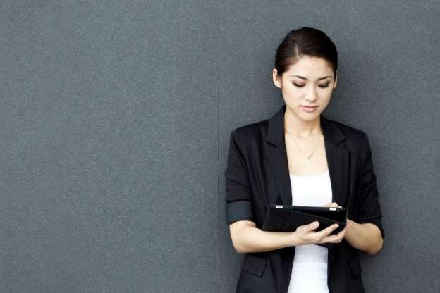 A person holding a tablet reads about competitive analysis