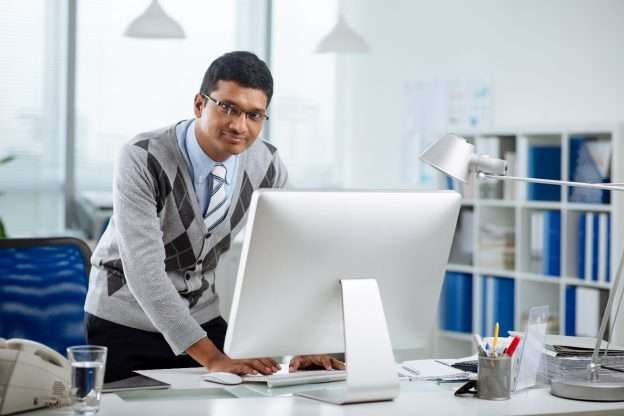 A man is looking at his computer as he works through the retirement plan selection process.