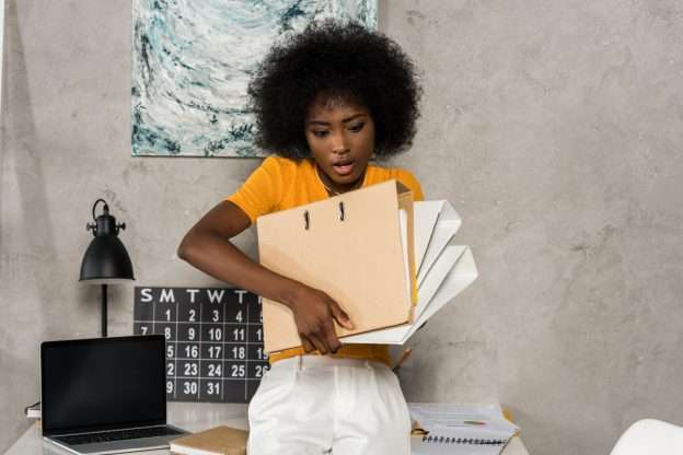 A woman is struggling to juggle tasks because she needs to delegate her work.