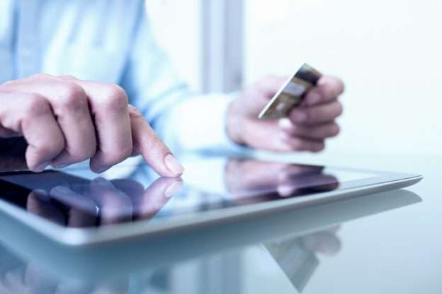 A person touches a tablet screen with one hand and holds a credit card in the other, determining which business expenses charged to the card are deductible for tax purposes