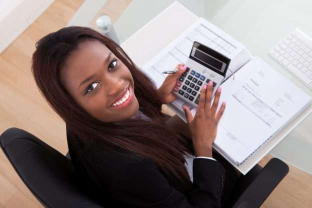 A small business accountant holds a calculator