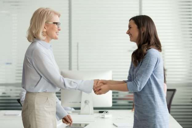 A person shakes hands to buy a business from another person to attain a competitive edge