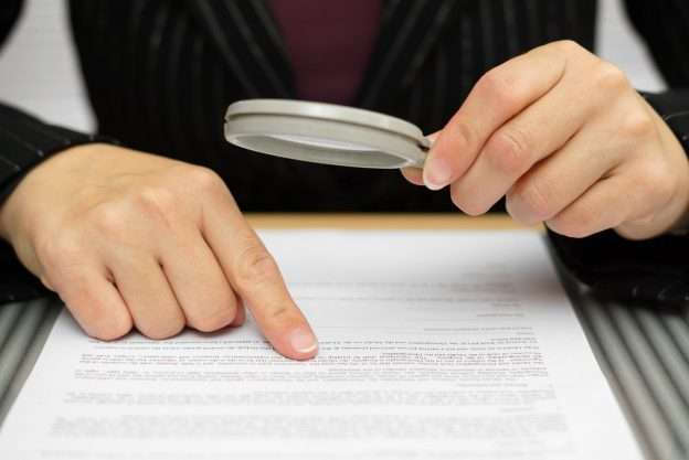 A person holds a magnifying glass to review the terms of their vendor contracts