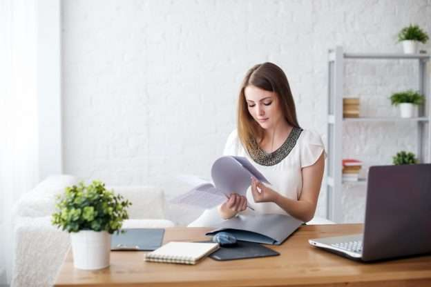 An owner of a small business sits at a desk reviewing a terms and conditions document