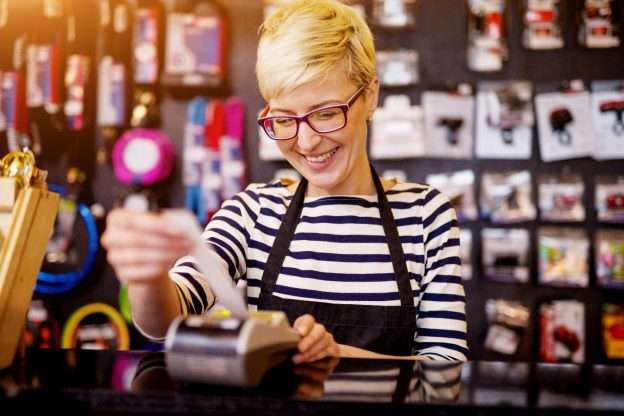 A person at a cash register studies her small business sales tax requirements