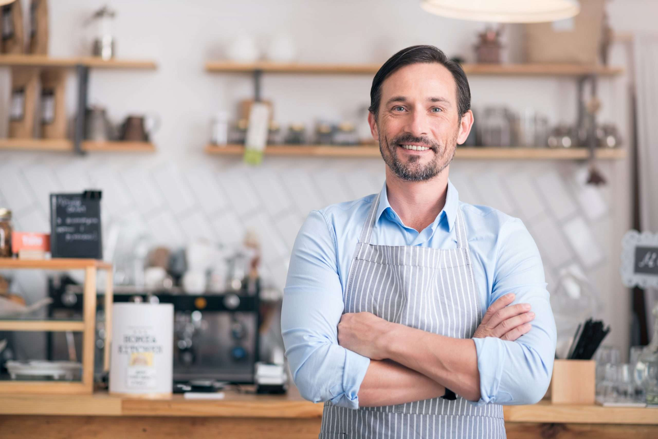 A cafe manager smiles confidently after starting a business