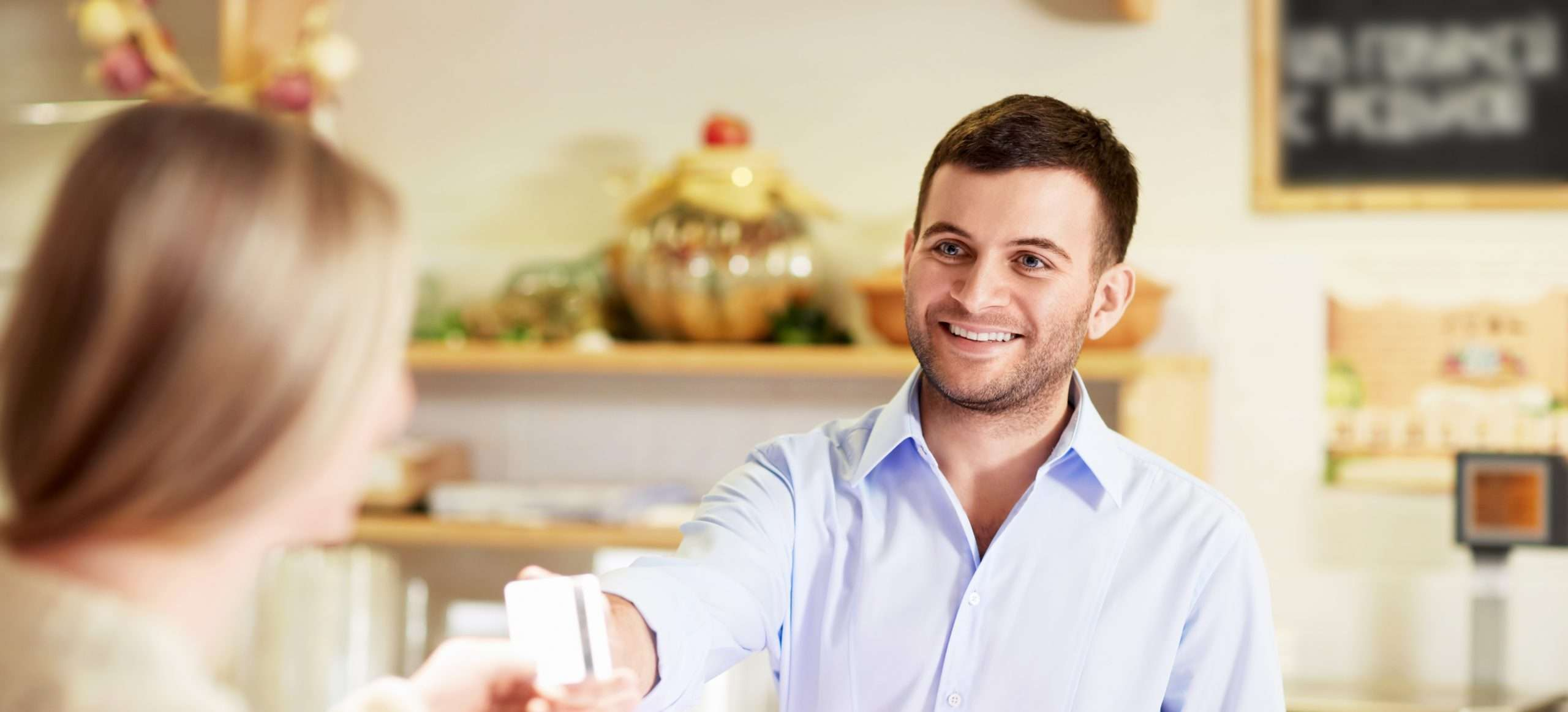 Two people exchange a credit card while using point-of-sale systems