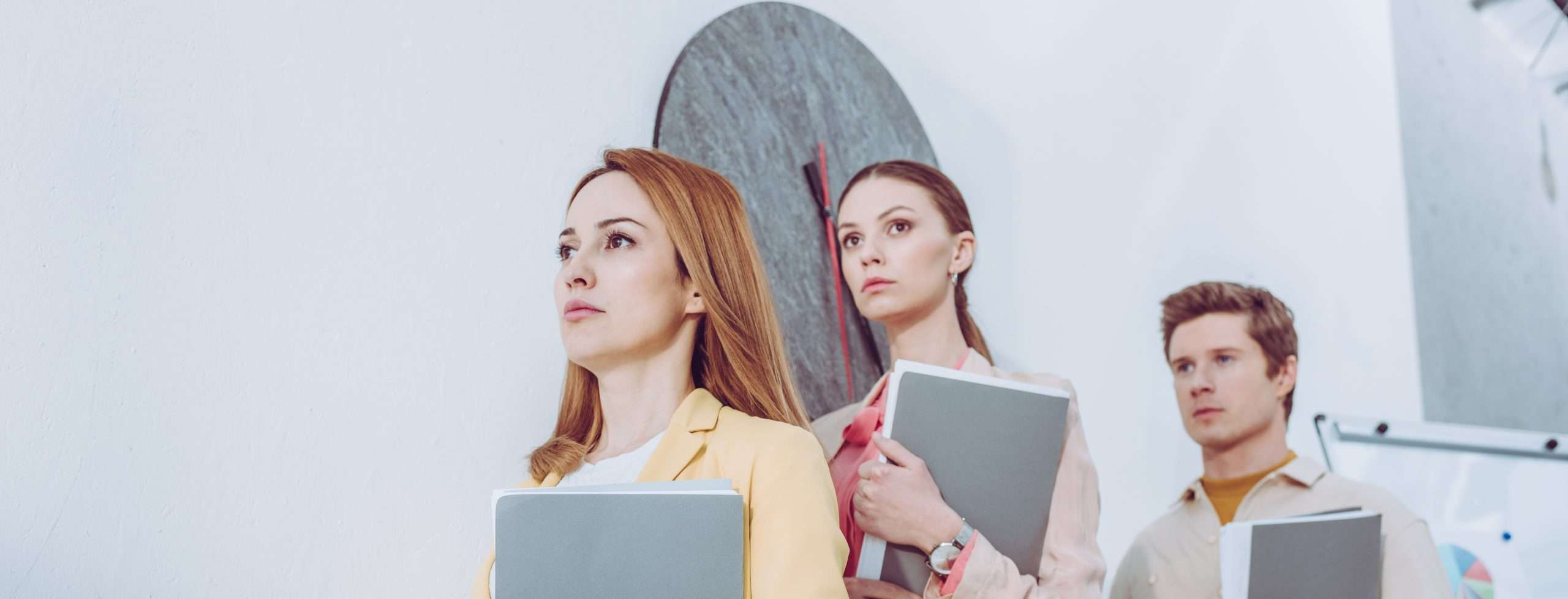 Three job candidates, sourced and selected with applicant tracking systems, hold folders while waiting in line