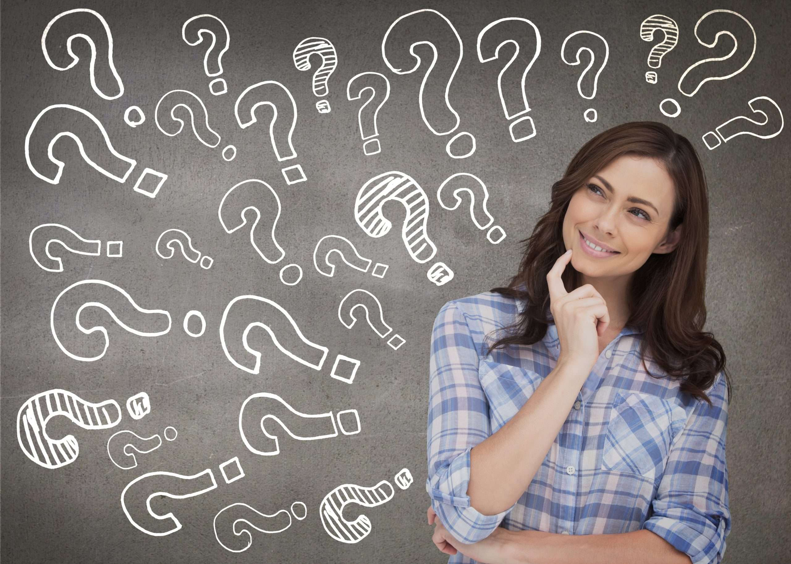 A person looks thoughtfully at a series of question marks while thinking of a name for a business
