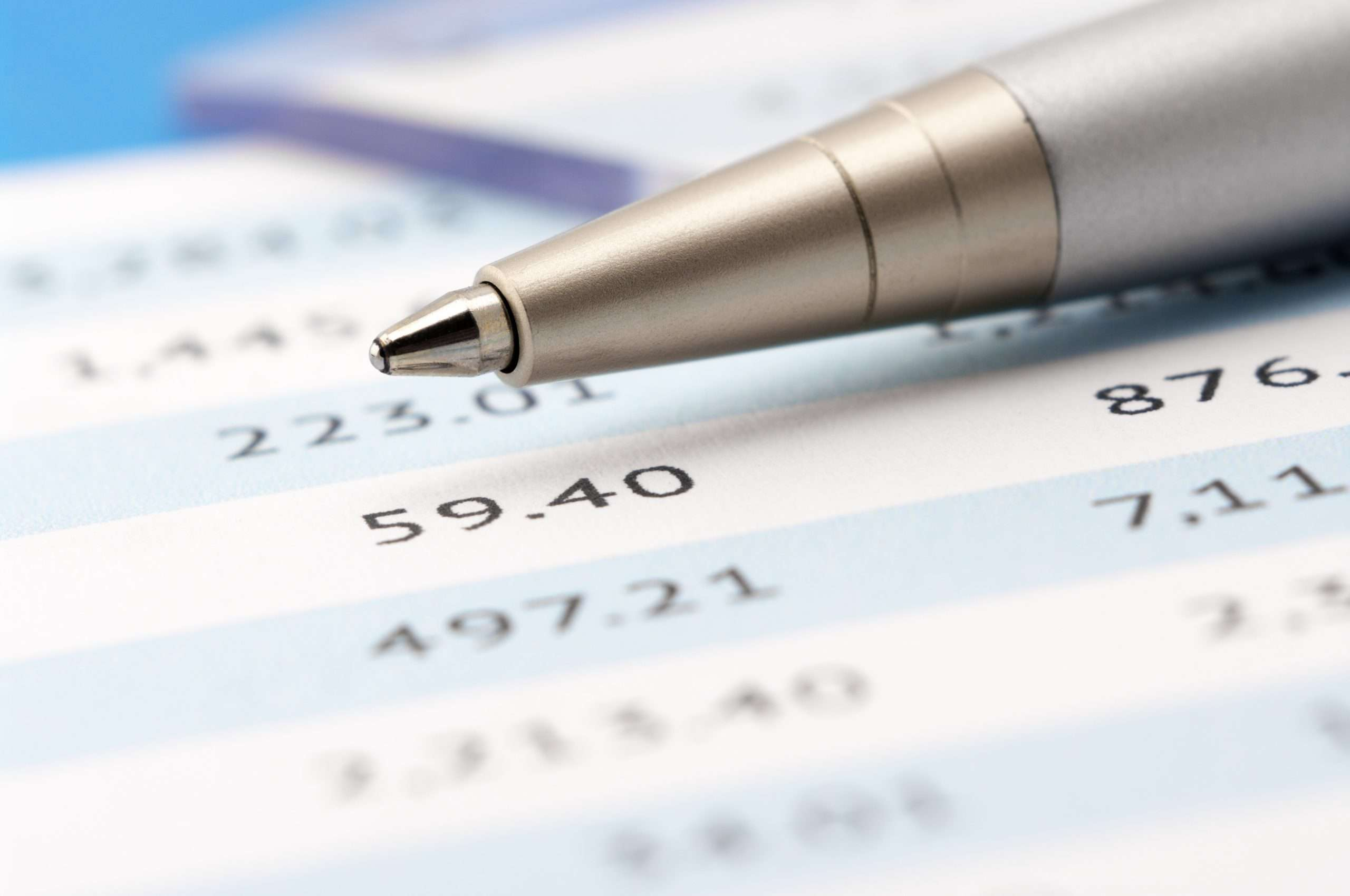 A pen lays atop a financial document used for evaluating the asking price of a business.