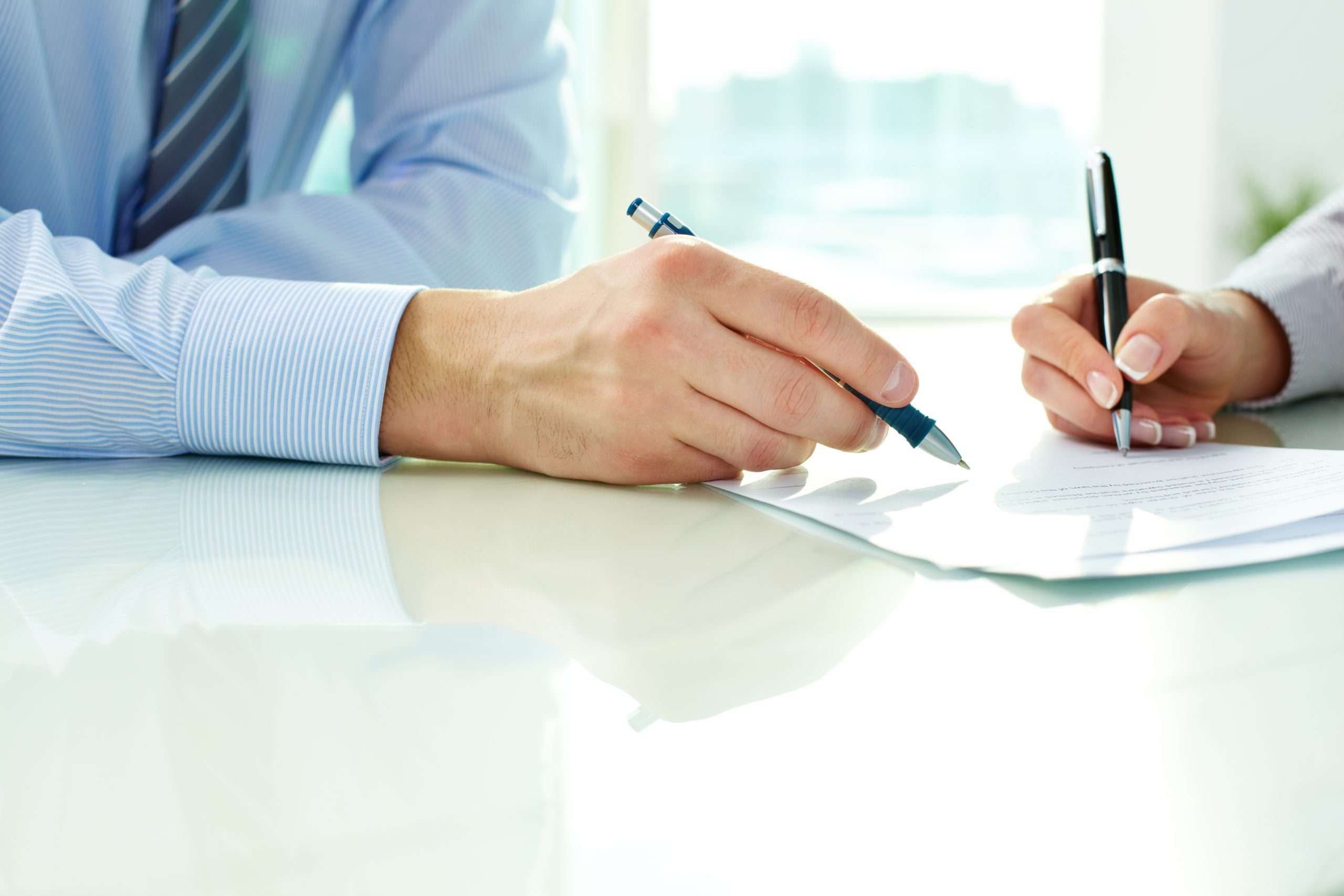 An attorney and a business owner work through a business broker's agreement.