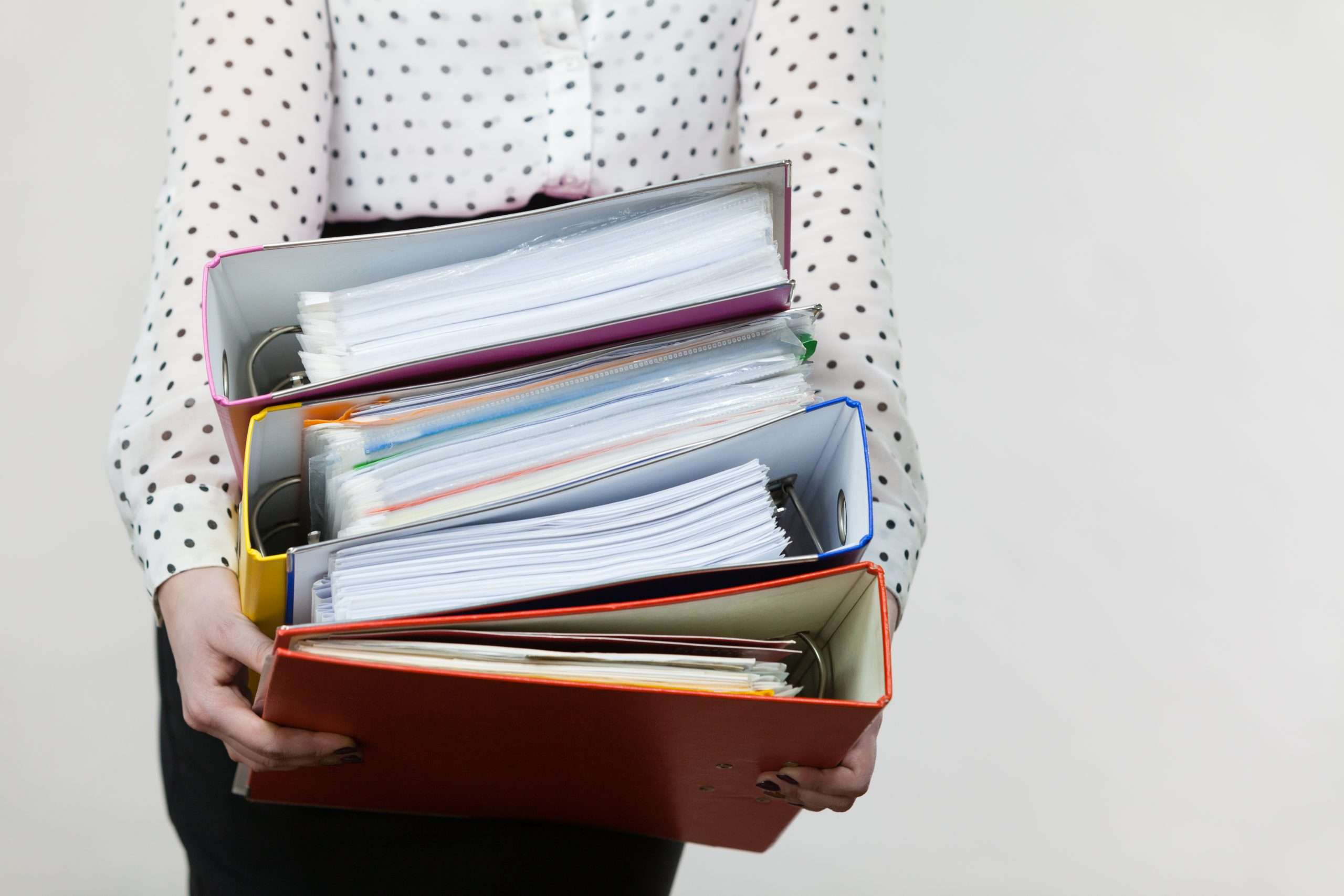 A person carries a stack of folders that may be useful in helping a business buyer complete the due diligence process.