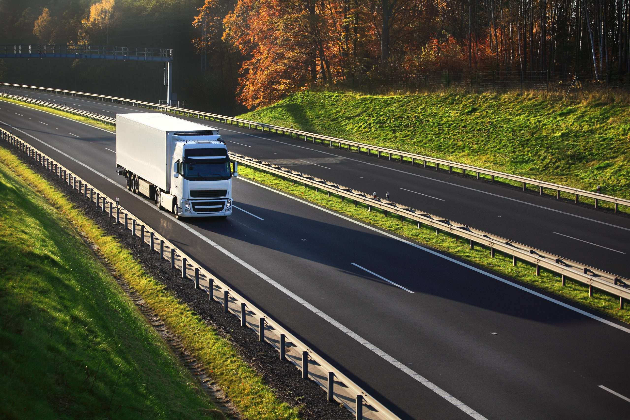 A delivery truck travels along a highway to fulfill the logistics needs of shipping services.
