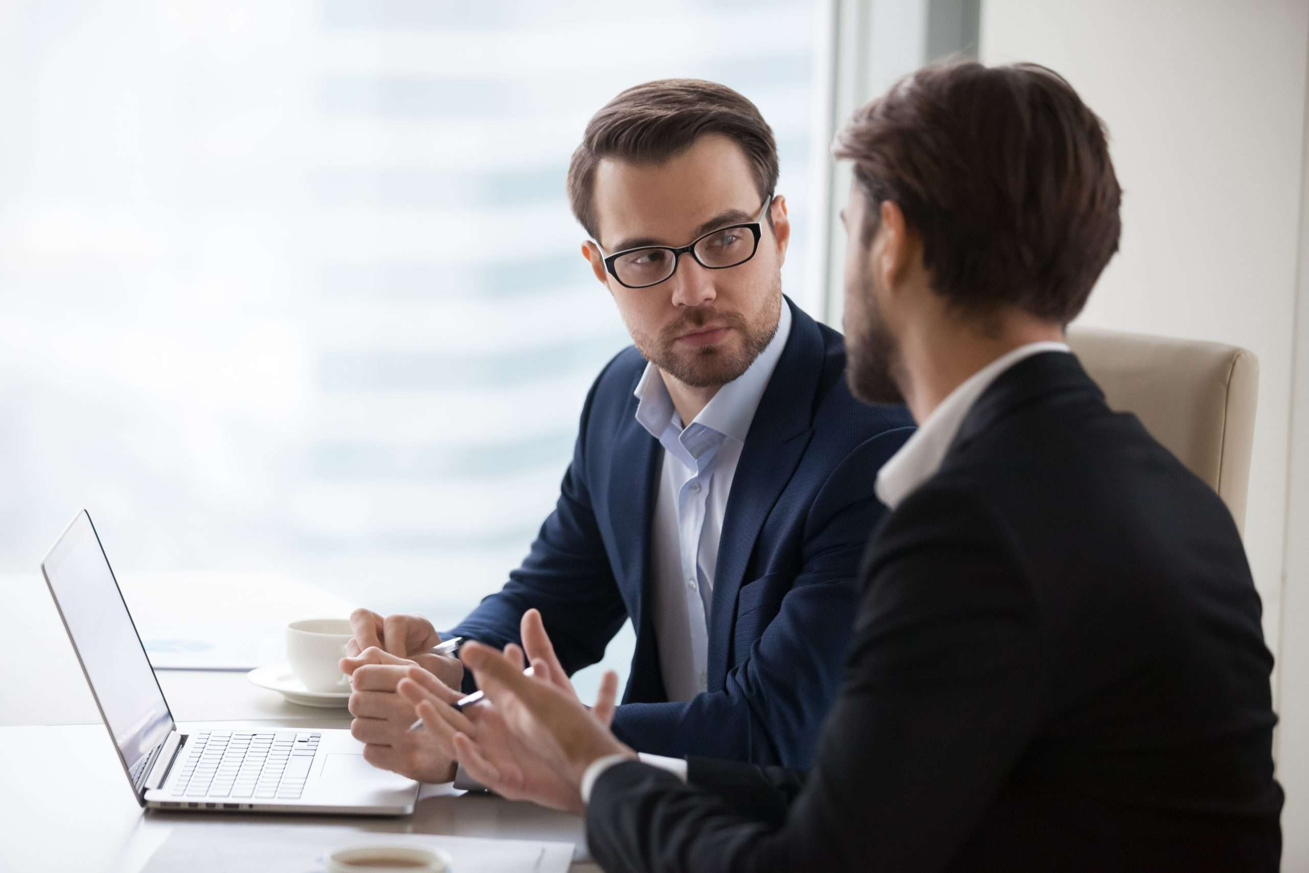Two people sit at a desk discussing buy-sell agreements