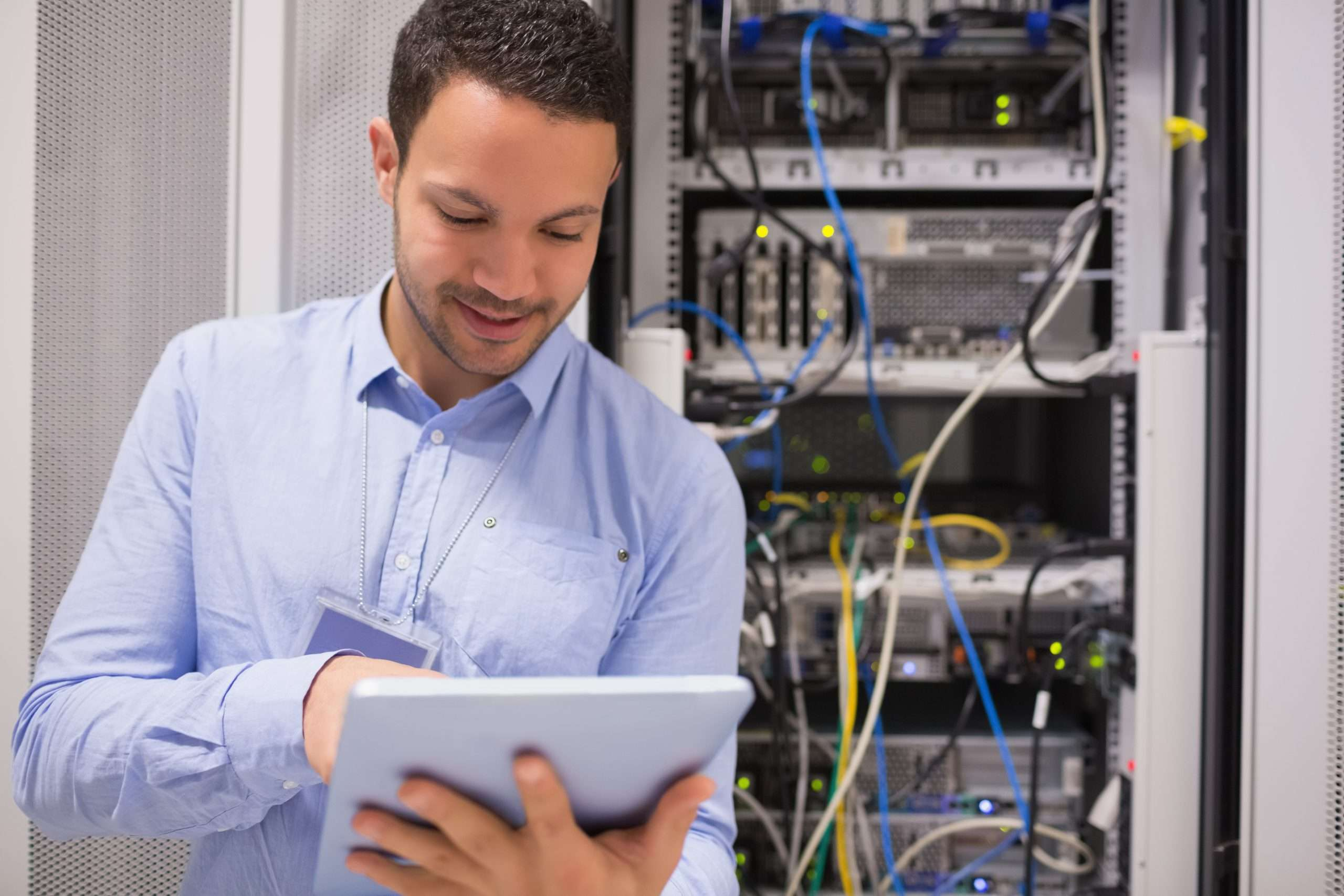 A person holding a tablet stands by a stack works to reduce technology downtime for a business