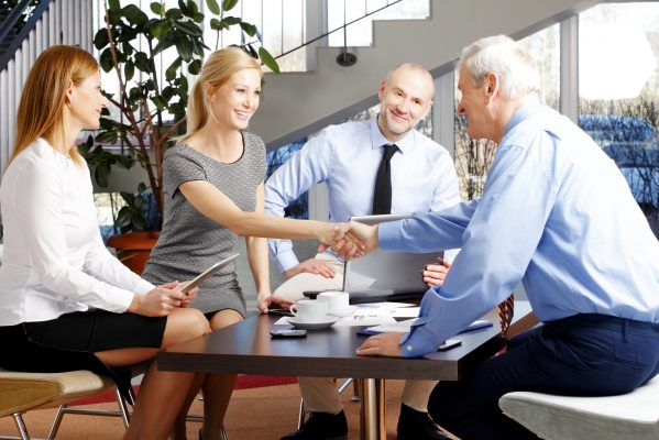 A seller, a new owner, and a team of professionals work through the steps of completing a sale of a business