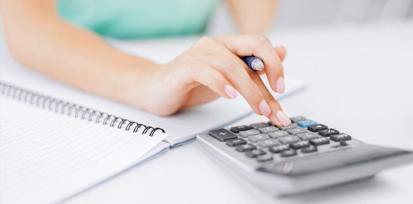 A person uses a calculator to determine whether a commercial bridge loan would benefit a business