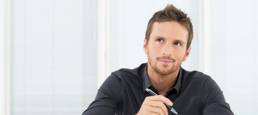 A person sitting a desk with a pen and portfolio considers whether to transfer the ownership of a business to a trust